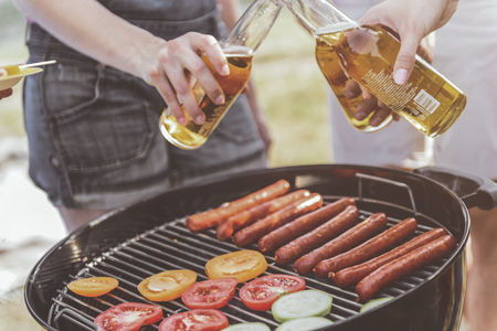 human hands clinking bottles of alcohol under grill. Vegetable and sausages are on grate. Close up