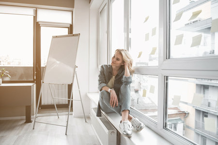 Meditative woman resting near casement in office. She is wearing casual clothing and smartwatch Imagens