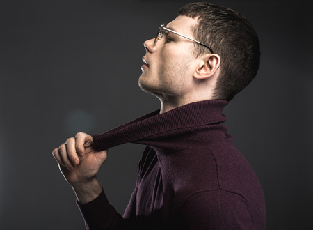 Side view male in modern glasses expressing seriousness while pulling collar. Gravity concept