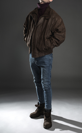 Male wearing modern coat, blue jeans and boots. Fashion concept Stock Photo