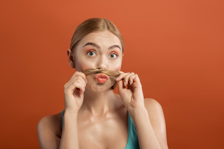 Portrait of well cared woman having fun with her lock while holding it between mouth and nose. Isolated on background Stock Photo