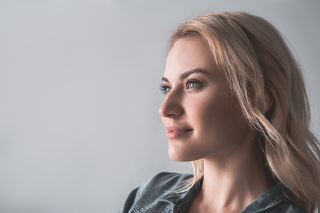 Profile of pensive woman with blonde hair looking aside. Copy space in left side. Isolated on background