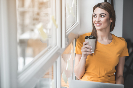 Portrait of good looking girl relaxing on windowsill with cup of beverage in hand. She is smiling. Copy space in left side