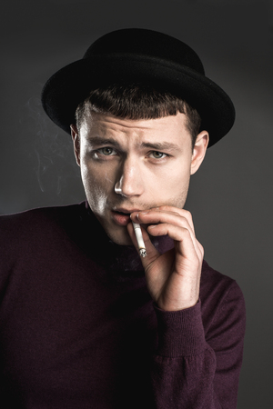 Portrait of gloomy man smoking cigarette. He isolated on grey background. Unhappy guy concept