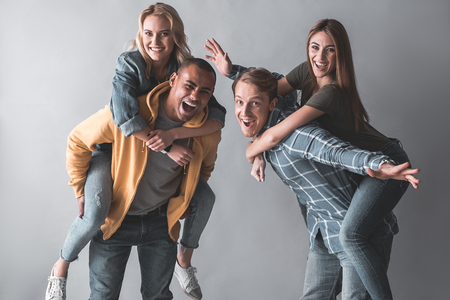 Portrait of happy students having fun. Men carrying girls on piggyback. Isolated on background