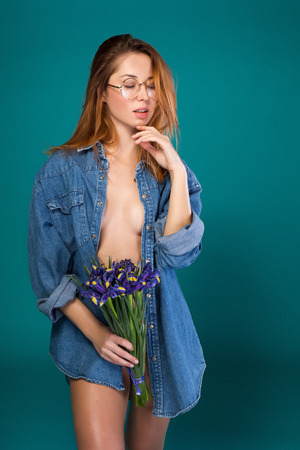 Portrait of sensual young woman touching her face while expressing desire. She is standing topless while wearing jacket and holding flowers. Her eyes are closed. Isolated Stockfoto