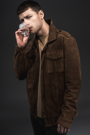 Portrait of demure male smoking cigarette. He isolated on black background. Tough guy concept Stock Photo