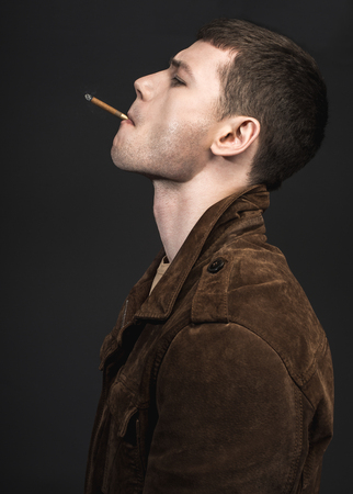 Side view pensive male piping cigarette. He wearing in modern jacket. He isolated on black background. Tough guy concept Stock Photo