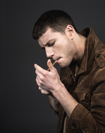 Side view serious male setting fire to cigarette. He isolated on black background. Demure guy concept