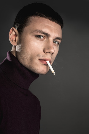 Portrait of wistful male holding cigar in mouth while looking at camera. He isolated on grey background. Muse concept Reklamní fotografie