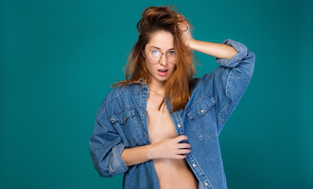 Portrait of sexy girl seducing while wearing only jean jacket. She is touching her red hair and looking at camera with passion. Isolated and copy space