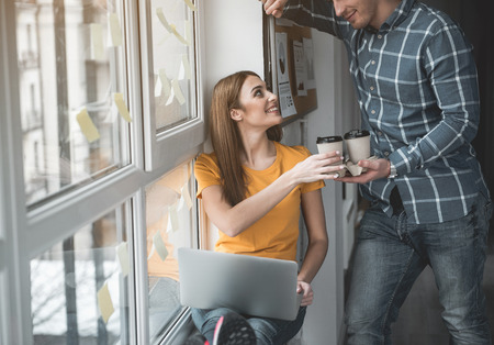 Enjoyed guy giving coffee to his partner at work. Woman accepting beverage with pleasure. Notebook is on her knees