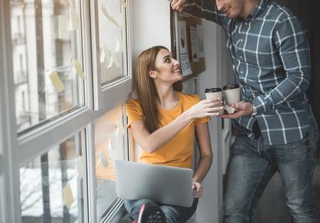 Genossener Kerl, der seinem Partner bei der Arbeit Kaffee gibt. Frau, die mit Vergnügen Getränk annimmt. Notebook liegt auf den Knien Standard-Bild