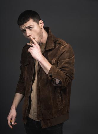 Portrait of assertive young man smoking cigar. He isolated on black background. Steepness concept