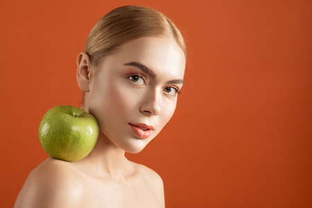 Portrait of beautiful woman without clothes staring at camera with tranquility. Green apple is on her shoulder. Copy space in right side. Isolated on background