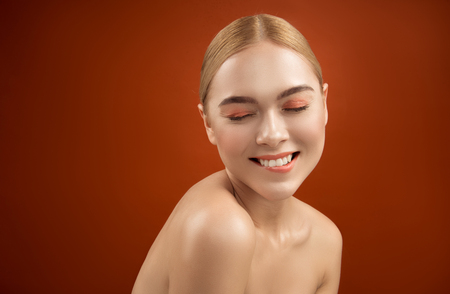 Portrait of pleased beauty being in good mood. She is posing naked and biting her lip. Copy space in left side. Isolated on background