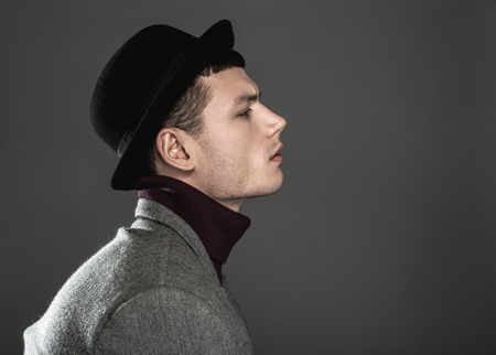 Side view pensive man wearing modern hat. He isolated on dark background. Copy space. Contemplative fashionable guy concept Imagens