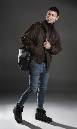 Full length portrait of cheerful man keeping bag in hand. Gladness concept
