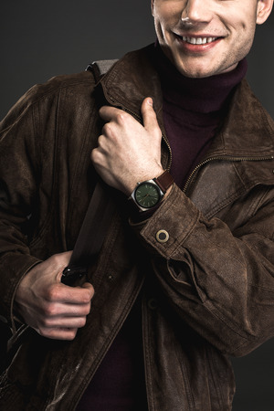Outgoing young male keeping bag in hands. He wearing modern watch. Gladness and fashion concept