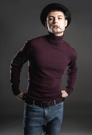 葉巻を発煙する卑劣な男の肖像画。彼は暗い背景で孤立した。保証の概念 写真素材 - 99771447