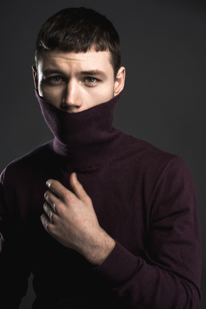 Portrait of worried male looking at camera while closing mouth by collar of sweater. Anxiety concept