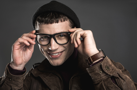 Portrait of cheerful handsome man wearing modern spectacles while looking at camera. He isolated on black background. Smiling stylish guy concept