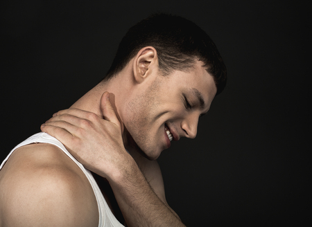 Side view beaming man touching neck by arm. He isolated on black background. Happiness concept Stock Photo