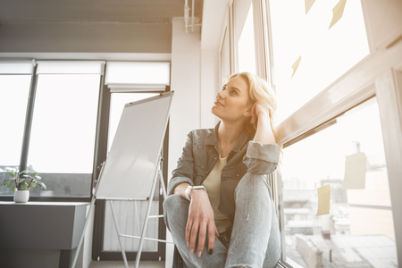Low angle of attractive girl with thoughtful expression sitting on windowsill and looking aside with wistfulness. Whiteboard on background