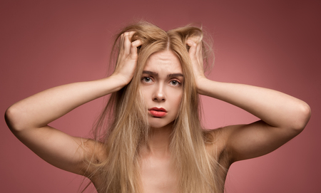 Portrait of disordered female person holding on to her head with disheveled locks. Isolated on rose background