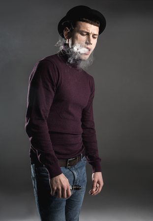 Portrait of melancholic man locating in fume while keeping gadget in hand. Unhappy guy concept Stock Photo