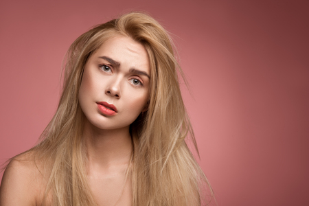 Portrait of discontent woman with untidy hair looking at camera with desperation. Copy space in right side. Isolated on rose background Stock Photo