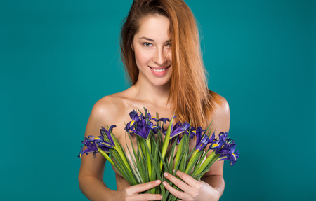 Natural beauty. Portrait of charming naked young woman holding flowers which covering her breast. She is looking forward with seduction and smiling. Isolated