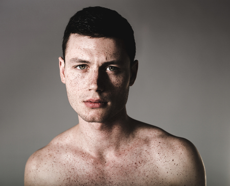 Portrait of orderly young man having many freckles. He isolated on grey background. Earnest concept Reklamní fotografie