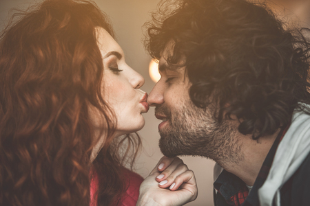 Love you. Sensual girl kissing nose of smiling guy with fondness. Their eyes are closed with pleasure Stock Photo