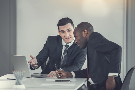 Smiling man talking with partner while gesticulating hand. Glad affiliate watching at screen of gadget. Cheerful employers working in office concept