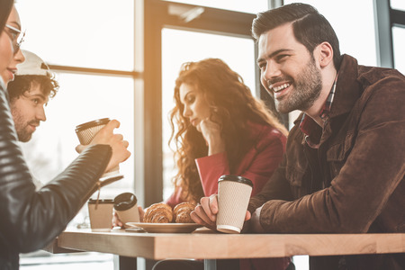 Cheerful young man and woman talking and laughing while drinking coffee. Their friends are getting bored on background