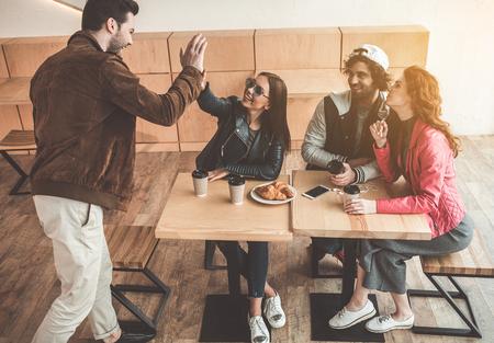 Hola. Alegre joven y mujer están dando cinco alta mientras se reúnen en la cafetería. Sus amigos están sentados a la mesa y sonriendo. Foto de archivo