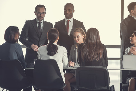 Concentrated businessmen standing near female colleagues while talking with them. They sitting at table in office. Communication during job concept