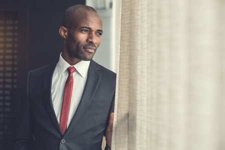 Portrait of pensive businessman looking at window while standing in office. Copy space