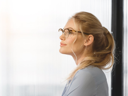 Profile of serene young woman planning her future career. She is standing near glass wall and smiling peacefully. Copy space Stock Photo