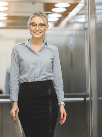 Portrait of confident young businesswoman going out the elevator. She is carrying papers with pen and smiling Stock Photo