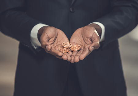 Close up hands of employer holding gold coins. Profit from business concept