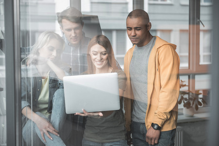 Four young people looking at laptop with happiness and interest. They are standing indoors