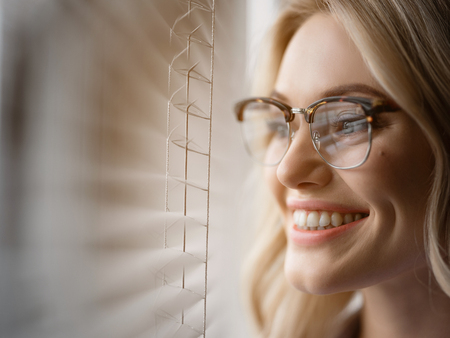 Close up of joyful young woman face looking over the window with interest and smiling. Hoping for bright future concept. Copy space