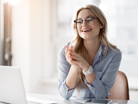 Portrait of happy young woman achieving great results in work. She is sitting near laptop and laughing