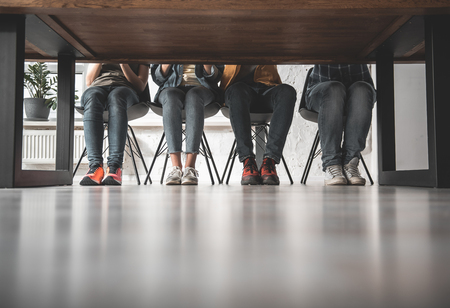 Four pair of legs sitting on chairs. Feet standing on floor together. Copy space Stock Photo