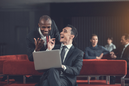 Outgoing employees laughing and gesticulating hands while looking at notebook computer. Positive affiliates resting in lounge zone concept
