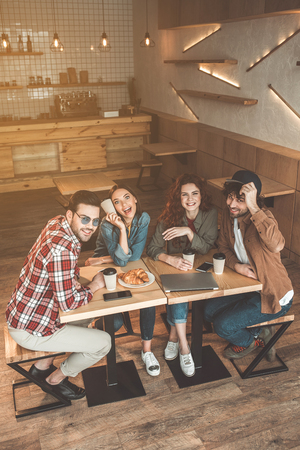 Top view of carefree guys and girls chatting in coffee shop. They are looking at camera and laughing Archivio Fotografico - 99950235