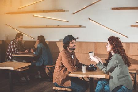 居心地の良いカフェテリアでデート幸せなカップル。熱い飲み物を楽しみながら話したり笑ったりしている。