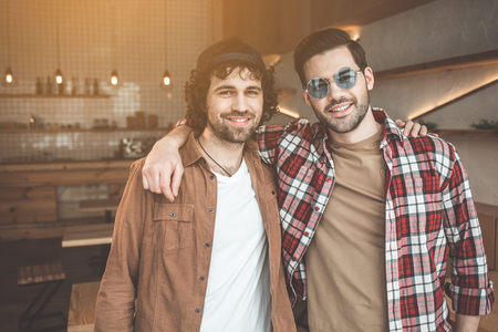 Best friends. Waist up portrait of happy two young men standing and embracing in cafeteria. They are looking at camera and smiling
